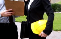 stock-footage-a-man-holding-a-clipboard-talks-with-a-woman-who-is-holding-a-hardhat